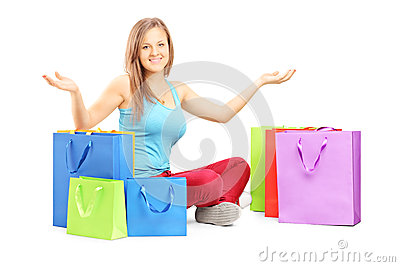Young smiling woman sitting on a floor with many shopping bags a