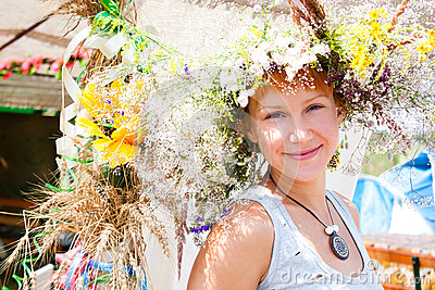 Young smiling woman with summer flowers wreath on head