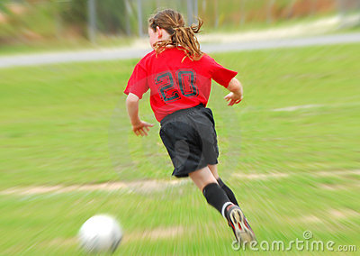 Young soccer player chasing ball