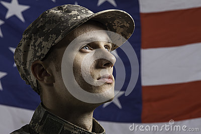 Young soldier posed in front of American flag, horizontal
