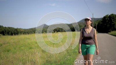 Young spanish woman walking on the road in a nice mountain landscape, slow motion footage stock video