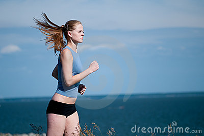 Young sport woman running on sunny day