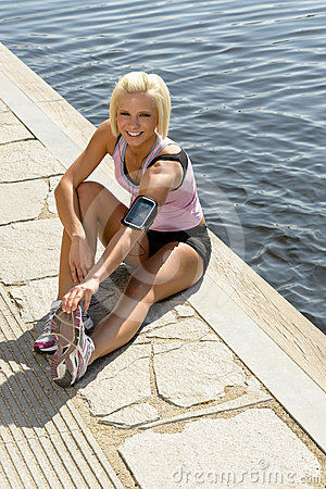 Young sport woman stretch legs water pier