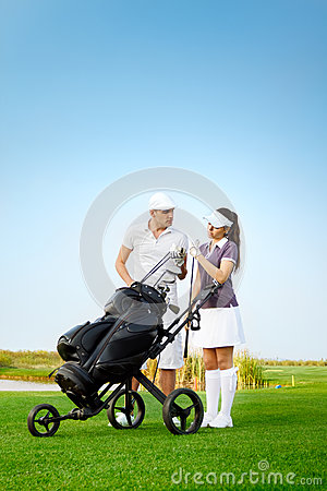 Young sportive couple playing golf on golf course