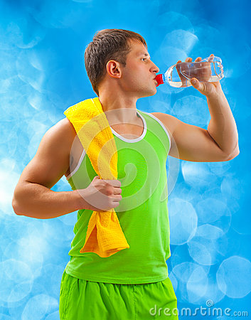A young sports man drinking water