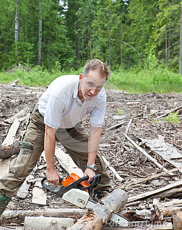 The young sports man in a light shirt green trousers and rubber boots works in the wood with a chain saw