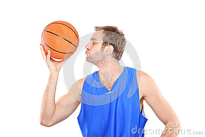 Young sportsman kissing a basketball