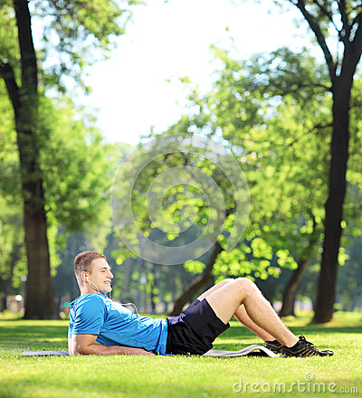 Young sportsman lying on a mat in a park