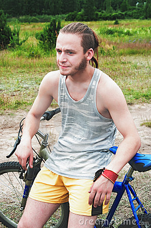 The young sportsman sits on a bicycle