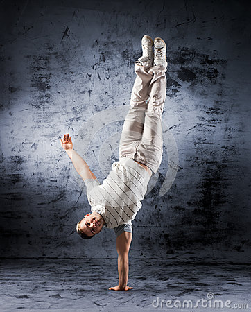 A young and sporty man doing a modern dance pose