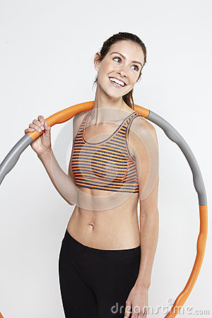 Young sporty woman standing with a hula hoop, smiling Stock Photo