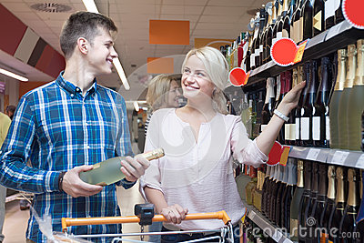 Young spouse buys wine in the store Stock Photo