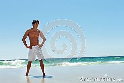 A young strong man posing at the sea shore