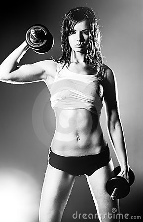 Young strong woman with dumbbells