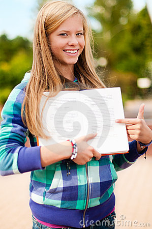 Young student girl showing something in book
