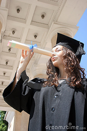Young student in gown looking through diploma