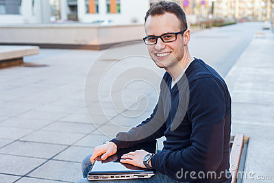 Young student sitting on a bench with laptop computer.