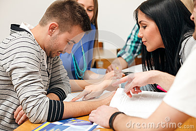 Young students sitting together with notes