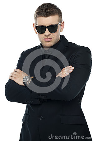 Young stylish bouncer in a black suit, arms folded