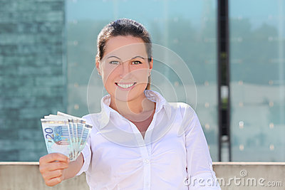 Young successful woman giving euro banknotes in the street
