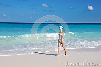 The young suntanned slender woman with a long fair hair in bikini goes on a peschenny beach against turquoise ocean