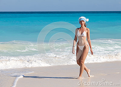 The young suntanned slender woman with a long fair hair in bikini