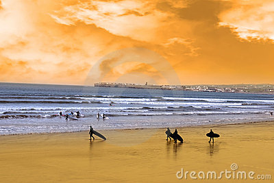 Young surfers walking on sunset beach