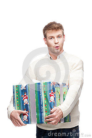 Young surprised man holding big heavy gift