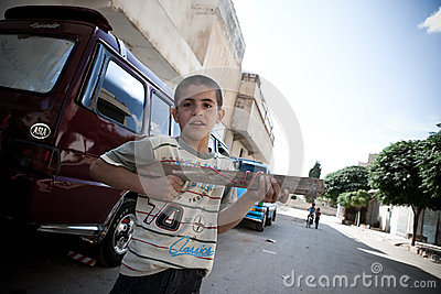 Young syrioan boy plays with wooden gun.Azaz,Syria. Editorial Stock Image