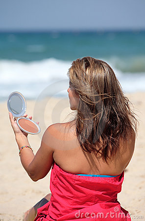 Free Young Tanned Woman Putting Make Up On Whilst On The Beach Stock Photos - 1794533