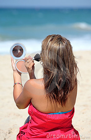 Free Young Tanned Woman Putting Make Up On Whilst On The Beach Stock Photo - 1794620