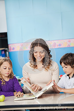 Young Teacher And Children Reading Book In