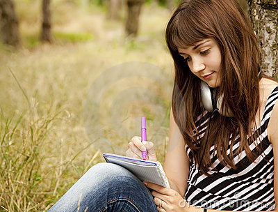 Young teen girl doing homework at the park