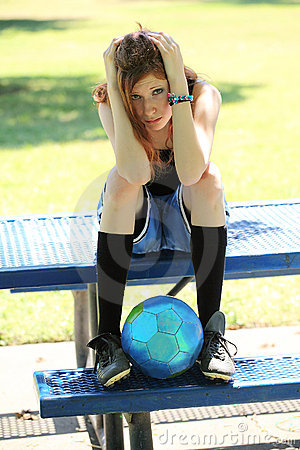 Young teen girl looking sad with soccer ball
