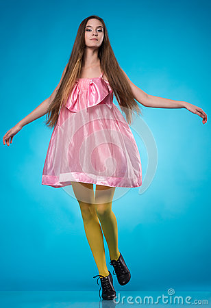 Young teen girl in a pink dress dancing