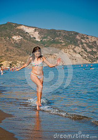 Young teen girl playing with waves at the beach.