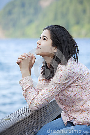 Young teen girl praying quietly on lake pier