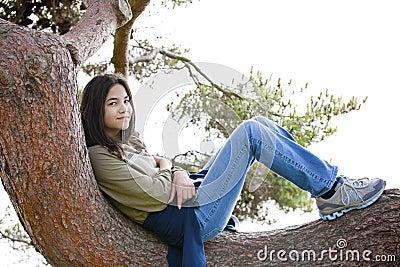 Young teen girl relaxing on tree limb