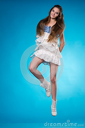 Young teen girl in a white lace dress jumping