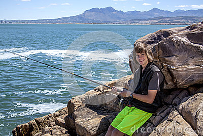 Young teenage boy fishing by the sea