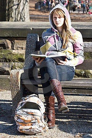 Young teenager girl sitting on a bench with book