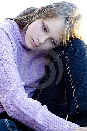 Young teenager girl sitting with sad expression