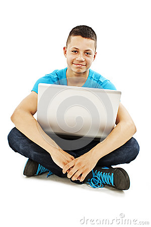 Young teenager with laptop sitting on the floor