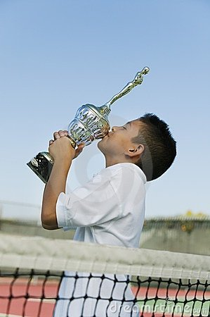 Young tennis player on court kissing trophy