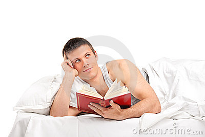 Young thoughtful man with a book lying on his bed