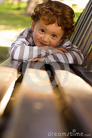 Young toddler lying on park bench
