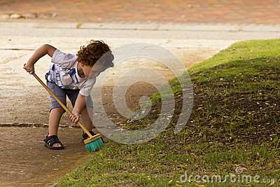 Young boy sweeping leaves from the driveway