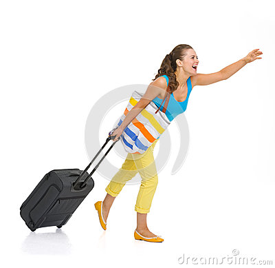 Young tourist woman with wheel bag catching taxi