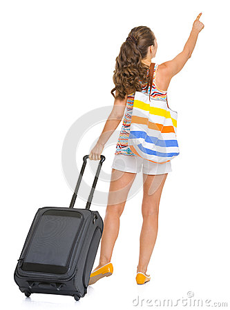 Tourist woman with bag pointing on copy space