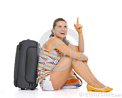 Young tourist woman with wheel bag sitting on floor
